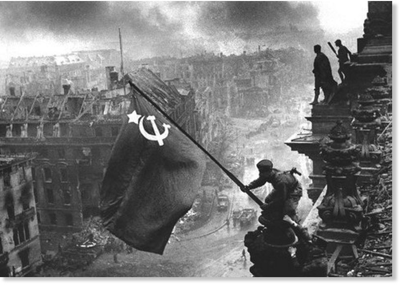 Merkel pred zidom : Kapitulacija pred Sputnikom V Rajhstag_zastava