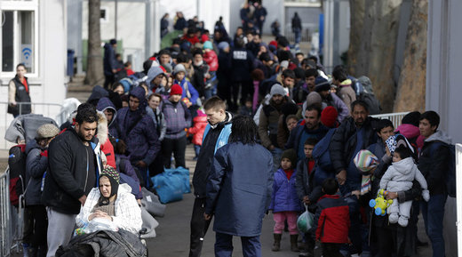 Migrants and refugees queue to board a train in the town of Sid, Serbia