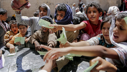 Yemenis present documents in order to receive food rations